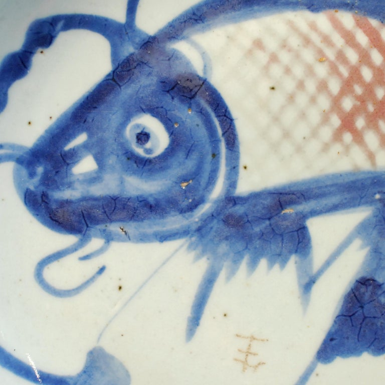 The fish on this hand painted 19th century provincial plate represents a blessing for wealth. Chinese symbols take on added meaning and nuance when combined with other motifs. The blue lines around the fish suggest water, which together would offer