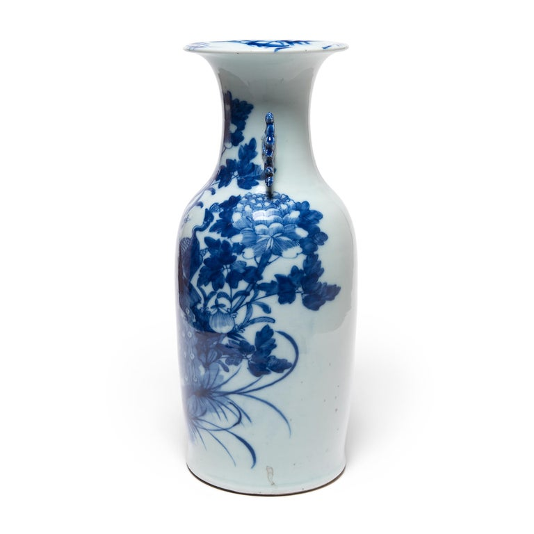 This 20th-century porcelain vase is an exquisite example of Chinese blue-and-white pottery. The vase is expertly formed with thin walls, widening to a flared lip and flanked by two molded scroll handles. Painted with richly saturated cobalt