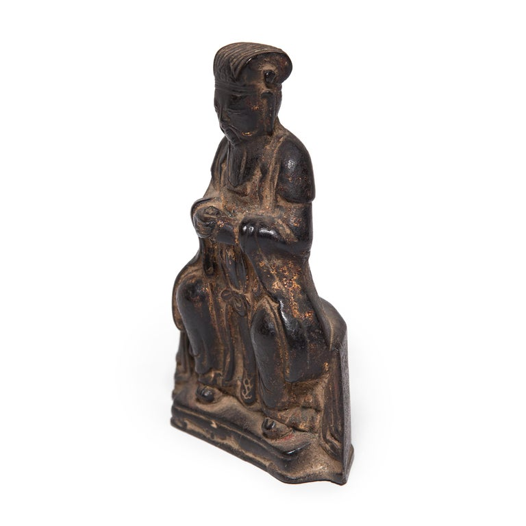 This early 19th century seated Daoist figure was once placed upon a traditional altar table to pay tribute to ancestors past. Cast in bronze, the figure's robes have a natural, elegant drape and the headpiece is exquisitely detailed. The seated