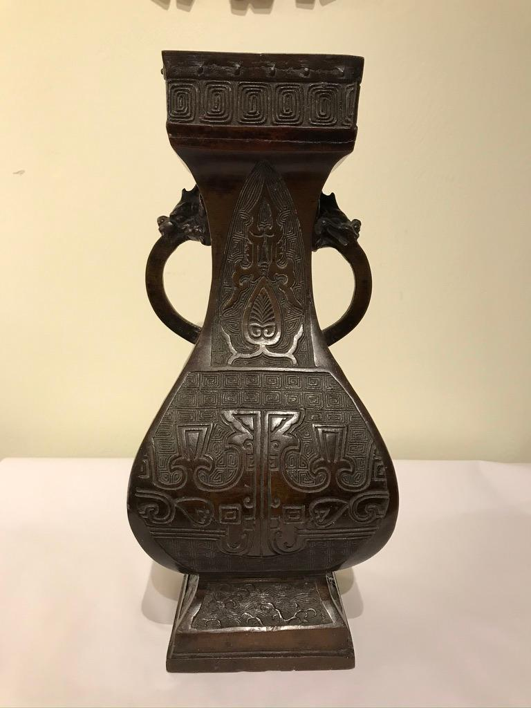 A handsome Chinese bronze two handled vessel with geometric top and base. The body decorated with etched Archaistic designs, the handles with dragon head terminals. This piece has a wonderful deep mocha patina. Stamped mark on base.