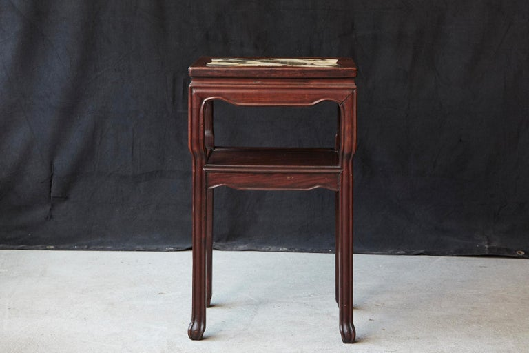 Early 20th century Chinese rectangular hardwood table with minimalistic molded carvings on the panels and legs, rectangular marble inset with rounded corners, one shelf and square legs ending in symbolic claw feet. There are some minor flaws to the