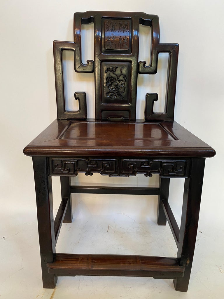 A 19th century antique Chinese heavily carved rosewood chair with lotus, rosewood apron with