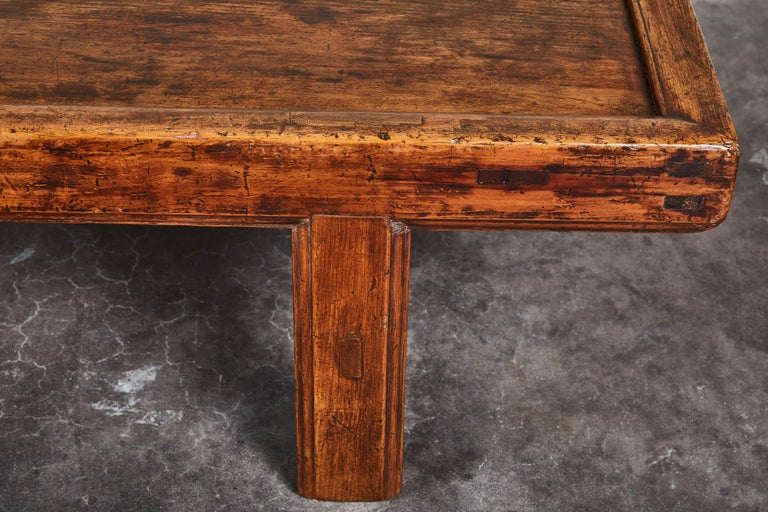 A simple 19th century Chinese low table, with an overall rustic patina. Clean, simple stretchers on four straight legs. Minor cracks and nicks on bottom corners, consistent with age. Top is even in patina and surface. Would make a great textural