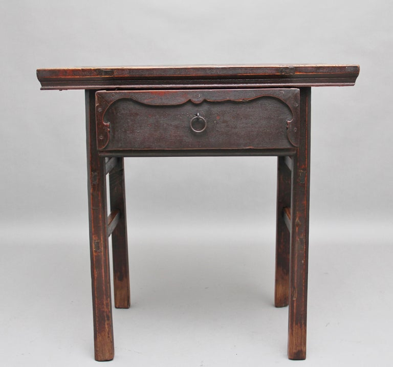 19th century Chinese elm side table, the rectangular top above a single drawer with carved decoration on the drawer front with original brass ring handle, standing on square legs united with side stretchers, circa 1880.