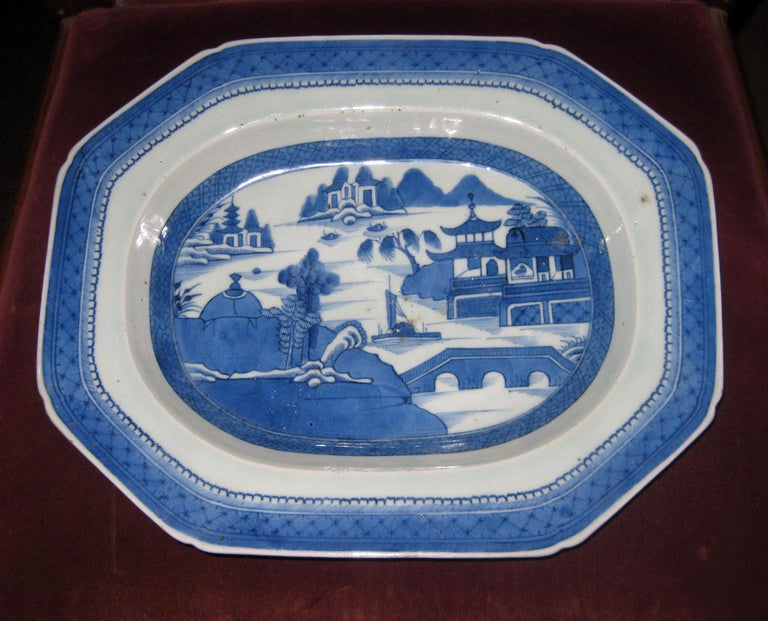 Canton deep octagonal shaped platter decorated in an under-glazed blue with a traditional Chinese hand decoration set against a white porcelain ground. The bottom rim of the platter is unglazed. Canton porcelain was manufactured and fired in the