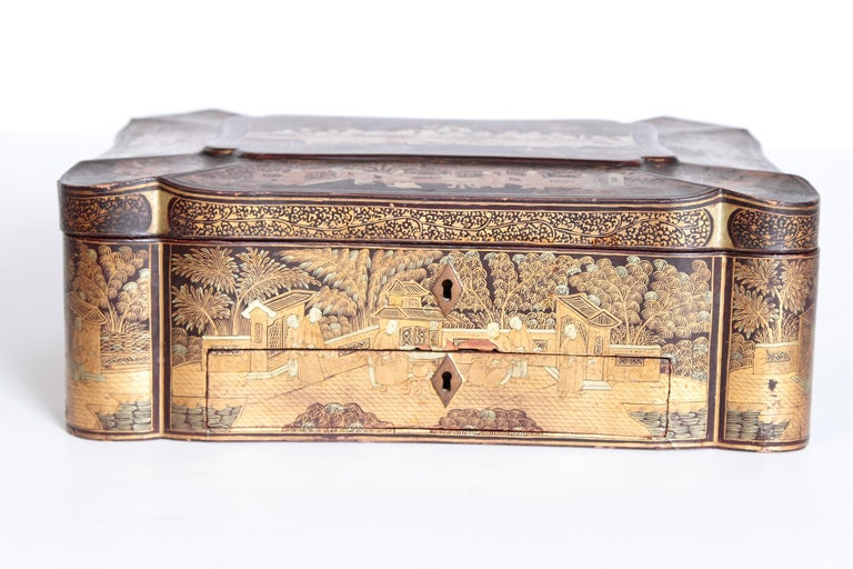 A beautifully executed black lacquer sewing box made for the English market. The rectangular shaped box has gilt chinoiserie overall with handles and a scalloped paneled lid. Fitted interior with bone pieces intact.