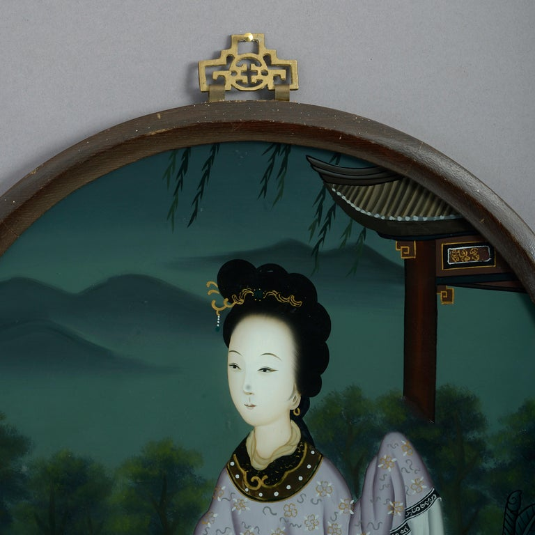 A late 19th century reverse glass painted portrait of a lady, by a pagoda within a mountainous landscape. Set within a circular wooden frame with pierced brass hanging plate.