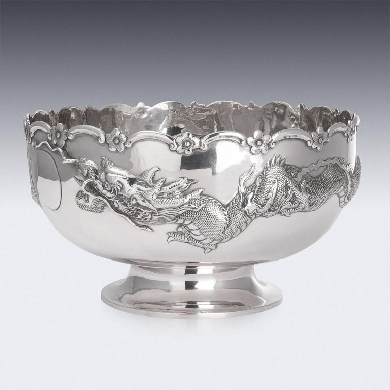 Antique late-19th century Chinese export solid silver bowls, very large and of traditional form, hand chased with a large dragon in relief chasing the pearl of wisdom, the design is particularly well modelled and detailed, the growling face applied
