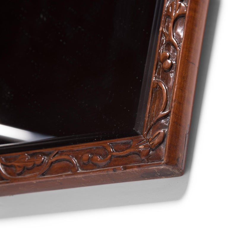 This contemporary bevelled mirror is set in an antique walnut frame hand carved with a flowered trailing vine motif. Chosen for its rich color and open grain, walnut was the ideal wood for realizing the high level of workmanship characteristic of