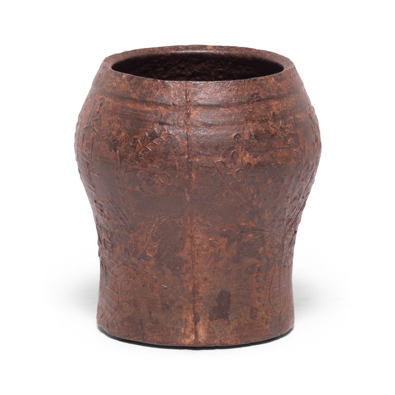 Cast in iron with a raised floral design, this vintage mortar was originally used in a traditional Qing-dynasty apothecary to create herbal medicines. The swelling shape allowed free movement of a pestle to effectively grind, mash, and macerate