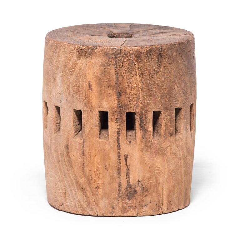 Carved from a single block of Elmwood, this unusual piece was once part of the central wheel shaft of a Qing-dynasty grain mill. Each slot once secured a peg of a large water wheel, which harnessed river currents to draw a millstone across grain