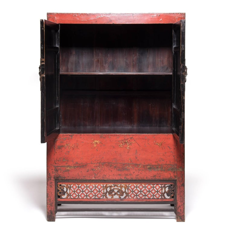 This red lacquer cabinet is an excellent example of the rich, decorative style of cabinetry built during the 19th century in China's Shanxi province. Traces of the original gilt paintings depicting vases with auspicious flowers remain. The