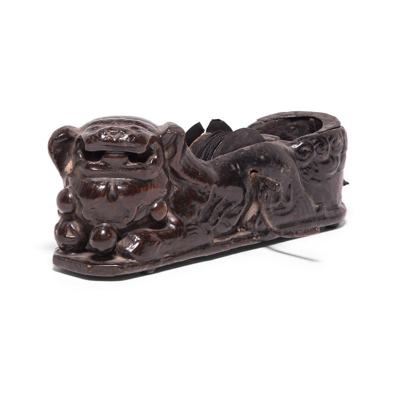 Given the beauty and thoughtful design of traditional Chinese furniture, it's no wonder that Qing-dynasty carpenter's tools were accorded the same attention to detail. This remarkably intact 19th century inkline reel is carved to depict a guardian