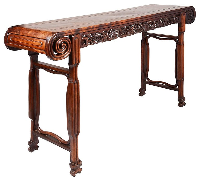 A good quality late 19th century Chinese hardwood alter table, having three inset panelled top, carved scrolling ends, the frieze with carved mythical dragons. End supports each with stretchers and terminating in scrolling carved feet.