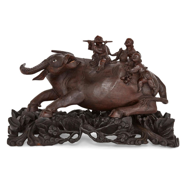 This carved hardwood sculpture of a cow with three children on its back is made from hardwood. The cow, wonderfully carved and chased with realistic textures, writhes underneath the three children, each of whom plays on his back—one playing a