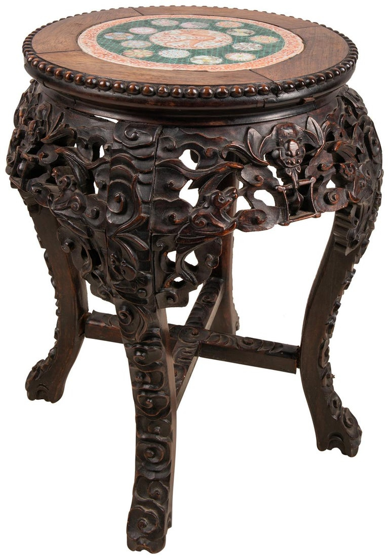 An unusual 19th century Chinese hardwood stand with hand carved foliate decoration, a Famille Verte porcelain plate inset to the center, depicting a mythical dragon, with a green ground boarder and classical motif symbols around.