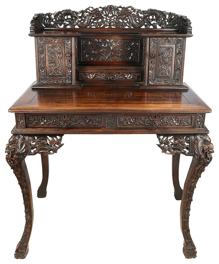 A good quality 19th century Chinese hardwood writing desk, having wonderful hand carved mythical dragons to the gallery, two cupboard doors and drawer all with carved blossom tree decoration, a polished writing surface, two frieze drawers, raised