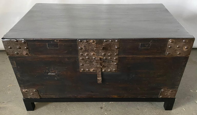 A very handsome Chinese lacquered trunk or coffee table with exceptional heavily embellished hand-hammered hardware -- iron handles, hinges, corner plates and lock which uses a cross piece or lock (not included) to secure the flat bolt. The chest is