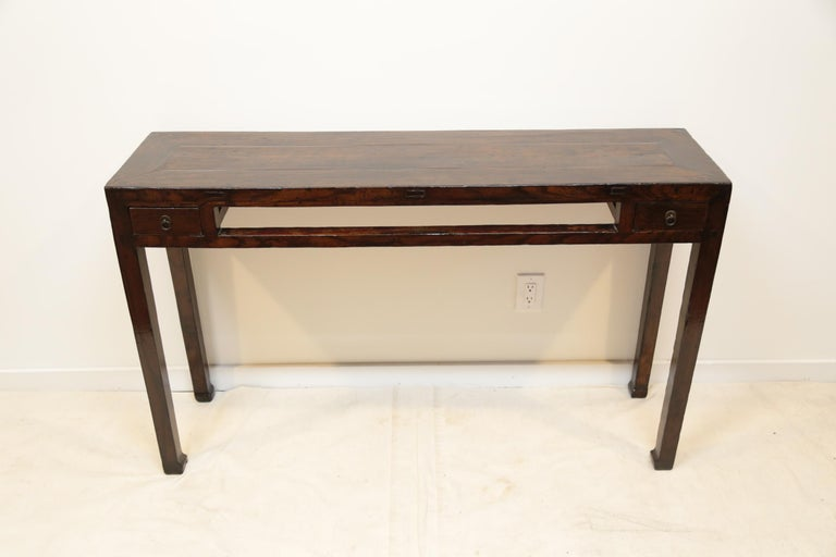 19th century Chinese console table. A minimal console table, with two small drawers and window strut. A elegant table with warm patina. Stands on horse hoof feet, circa 1880.