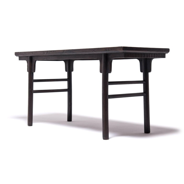 Achieving a modern aesthetic centuries in the past, this Qing-dynasty table's clean lines are at home in any contemporary room. The fundamental forms of antique Chinese furniture make up the backbone of minimalist design. The simple stretchers and