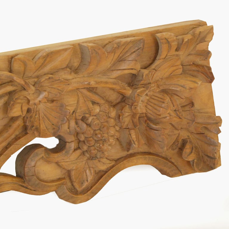 This architectural valance from the 19th century is beautifully carved in multiple dimensions with lotus, flora, and fruits on the vine and centered with a pearl of wisdom. It beautifully represents the masterful craftsmanship sought by 19th century