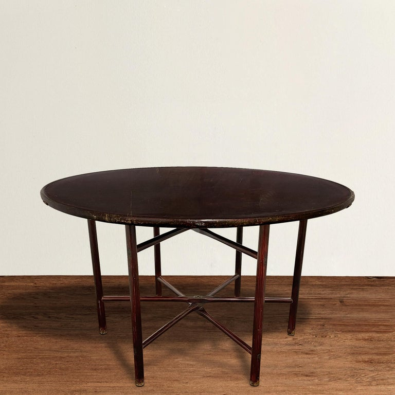 A chic and modern-in-spirit 19th century Chinese elmwood round table with a removable top and collapsible legs, and a fantastic dark sangre-de-boeuf lacquer. Legs can be an easily cut down to make the table standard dining height, or coffee table