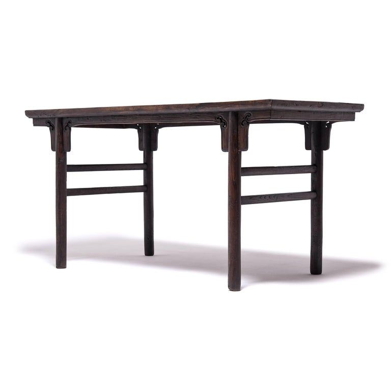 Achieving a modern aesthetic centuries in the past, this Qing-dynasty table's clean lines are at home in any contemporary room. The fundamental forms of antique Chinese furniture makeup the backbone of Minimalist design. The simple stretchers and