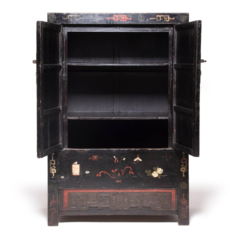 Seamlessly constructed and lacquered black, this spectacular Qing-dynasty cabinet provides the perfect blank canvas for dozens of painted scholars' objects, including vases, censors, brush pots, books and auspicious fruits and flowers. Still vividly