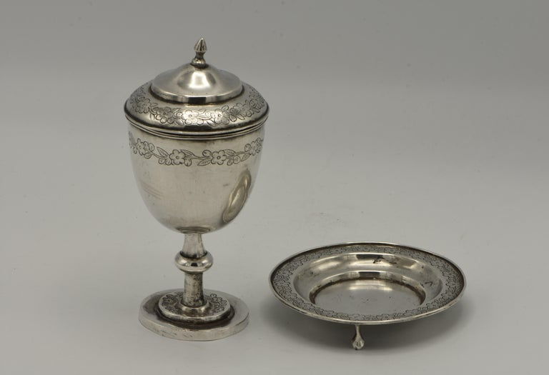 Chinese export silver covered Kiddush cup, 19th century.  Round bowl on baluster stem mounted to stepped and flat circular foot. Double domed cover with pointed finial. Engraved bands of imbricated leaves. Comes with the original footed saucer with