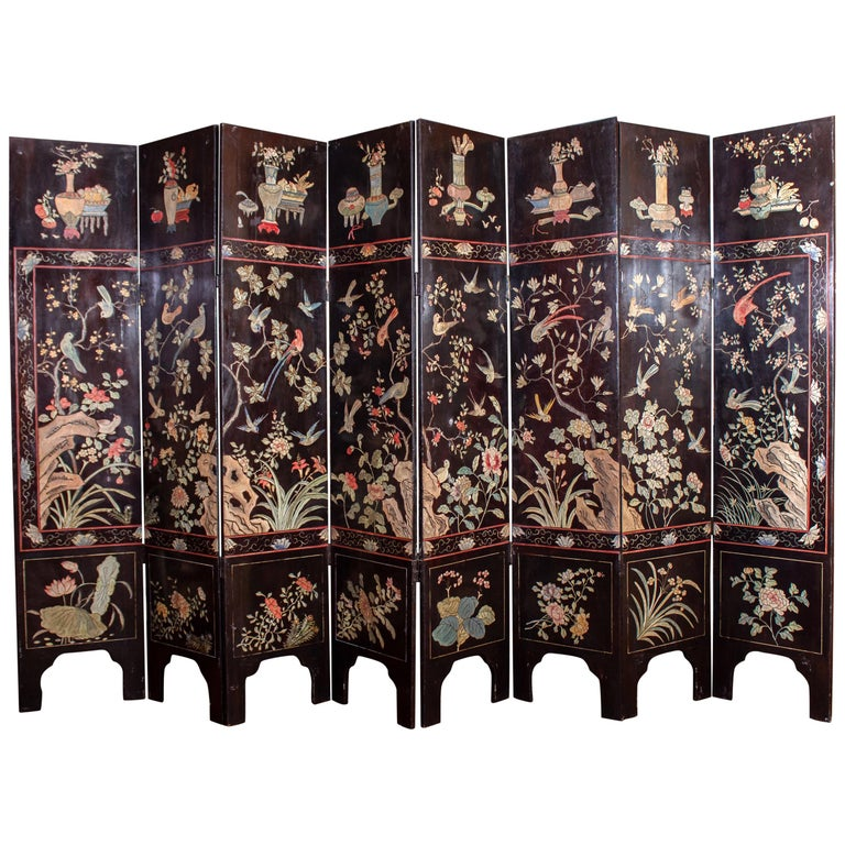 Outstanding double-sided eight dark Coromandel screen is decorated with polychrome landscape, detailed village scenes showing foliage, housing, walkways, and people-engaged in a variety of activities. The screen features a border with foliage,