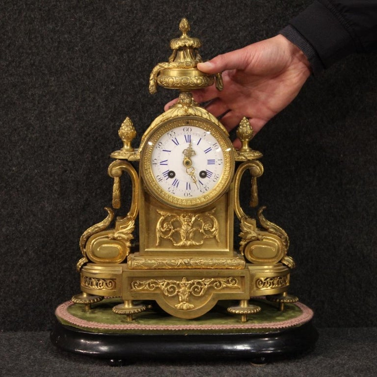 Italian clock from the late 19th century. Finely chiseled and gilded bronze and brass object with enamelled ceramic dial (see picture) and gilt and chiseled brass hands (see picture), complete with key. Clock with ebonized wooden base with velvet