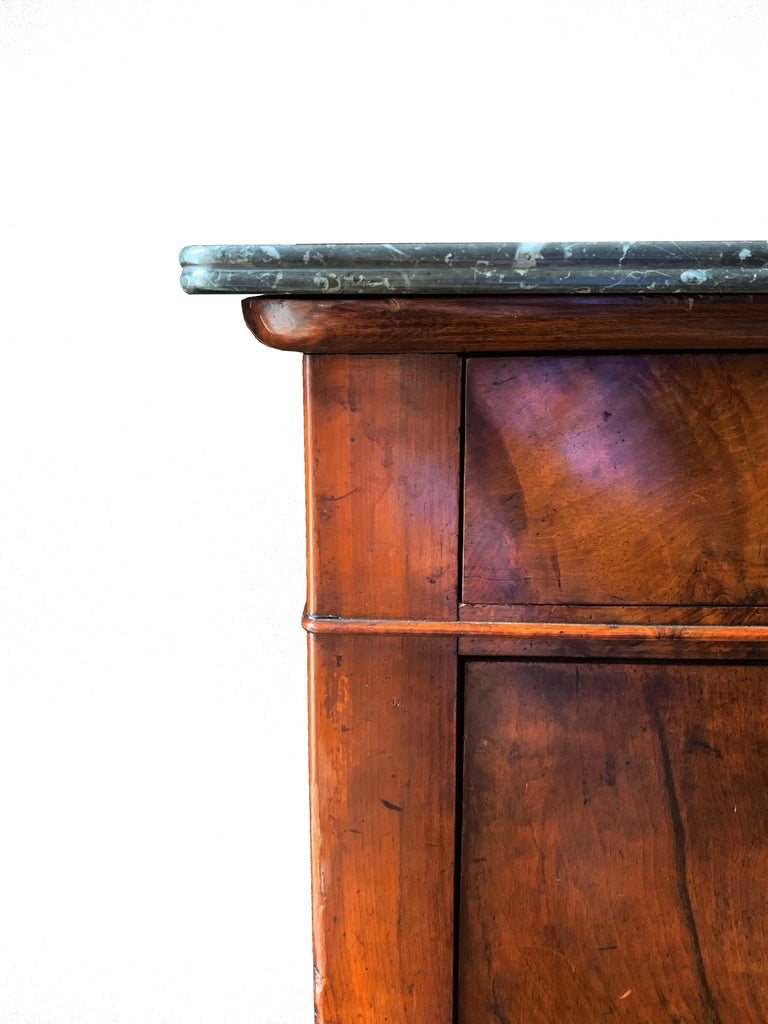 A dramatic Charles X fall front secretary in astounding burled walnut veneer. The original fossilized marble top is supported by an elliptical molding. The main body contains one upper drawer and three below the desk area. The secretary workspace