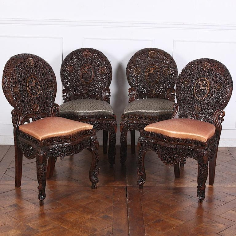 Unusual set of four pierce-carved Anglo-Indian chairs, completely covered with minutely-carved vines, leaves, flowers etc and a lion in the centre of each back, circa 1880.