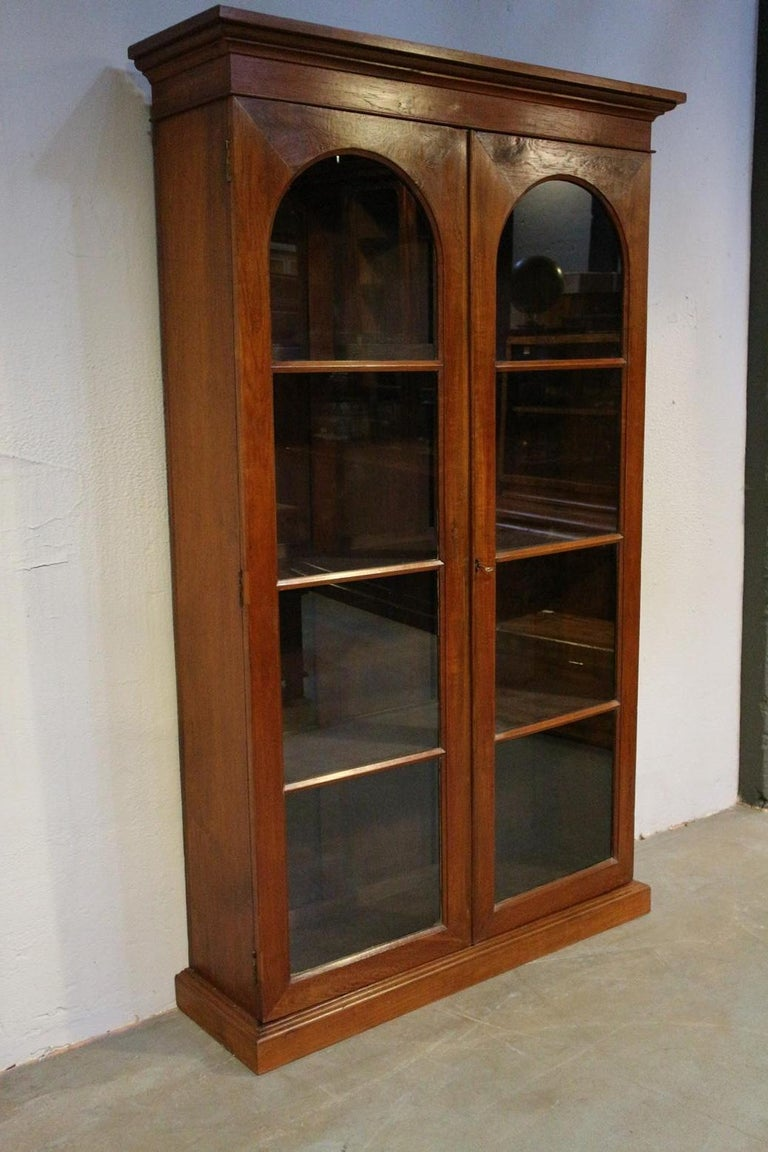 Beautiful sleek antique 2-door bookcase. Teakwood. The cabinet has adjustable shelves. Warm color. Entirely in perfect condition. Shelves are not original. Origin: Colonial India Period: circa 1880 Size: 122cm x 35cm x 220cm.