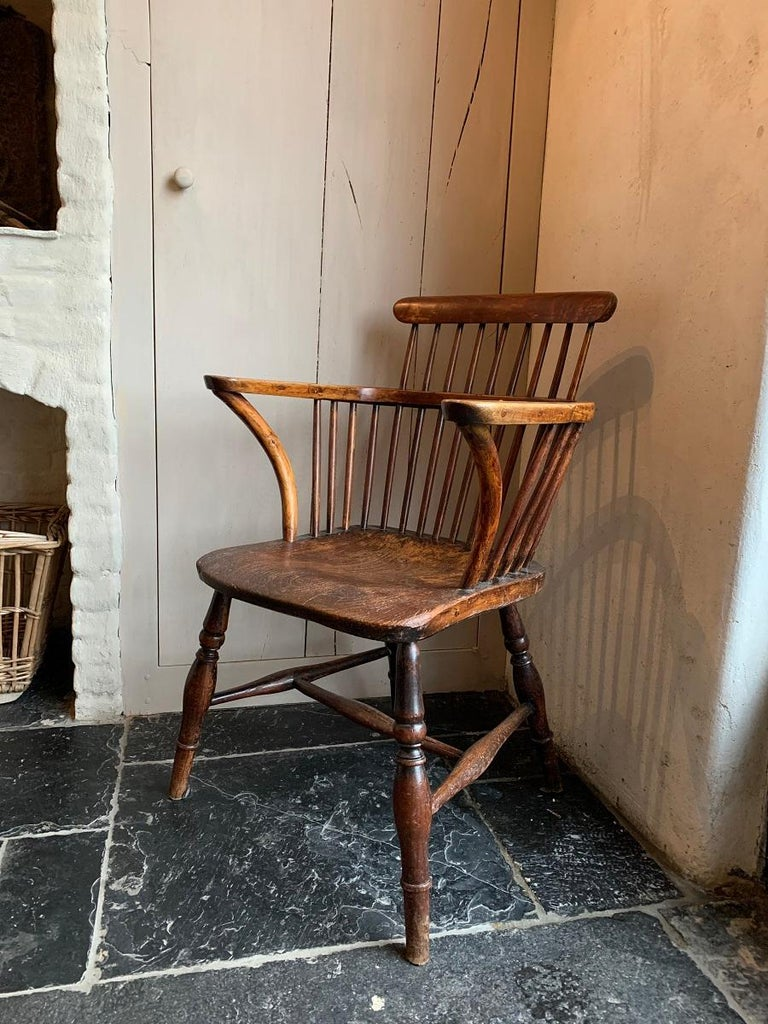 A rare early 19th century Windsor chair with a low comb back and widened armrest. All original with a one slab elm seat. As good as they get...