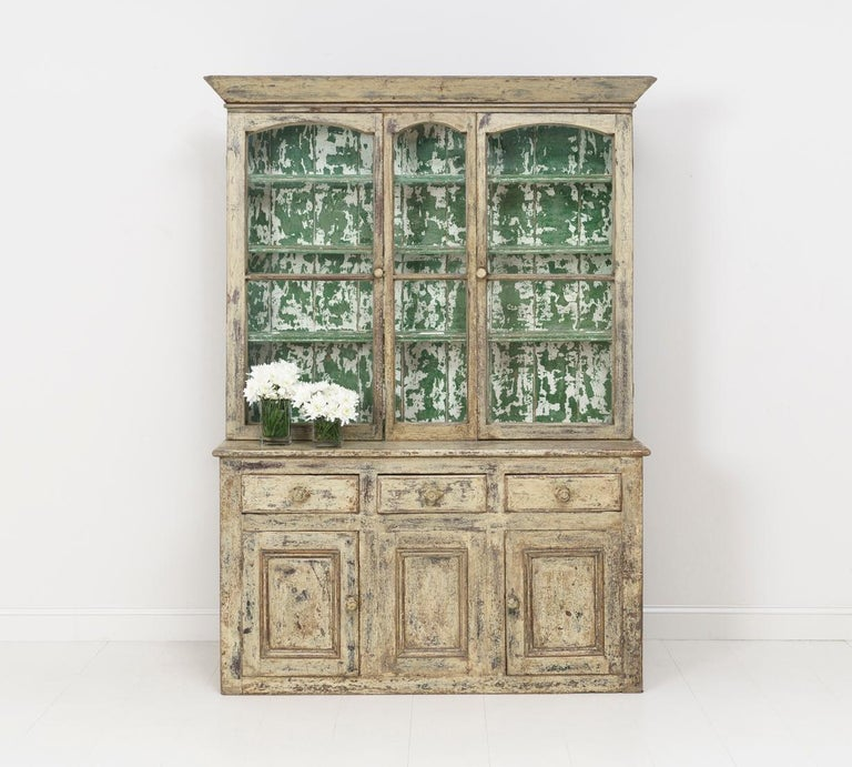 A rare Cornish vitrine cabinet from the 19th century with original patina and glass. This cabinet is a wonderful storage and display piece with loads of character. Measures: The upper shelves are 55.44 inches wide x 6.75 inches deep.