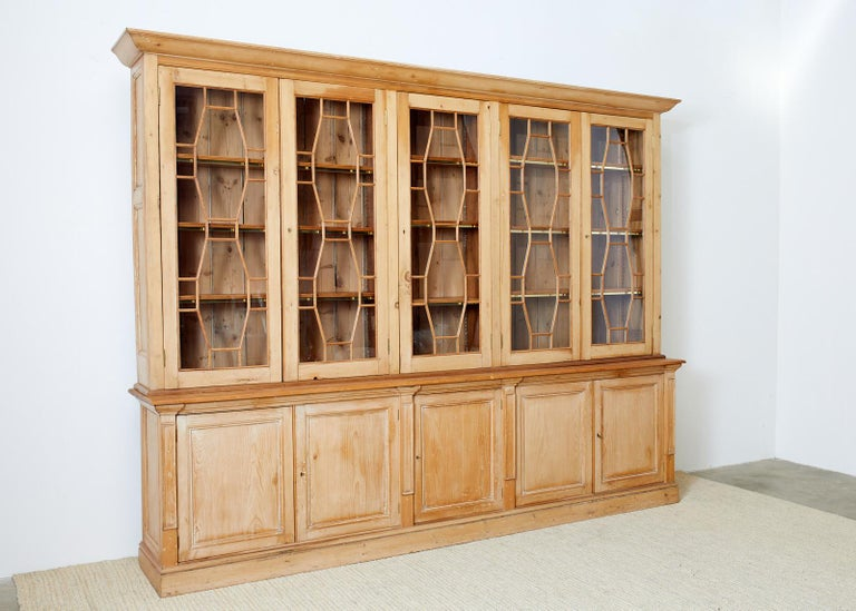 Grand 20th century country English library bookcase cabinet beautifully constructed from pine. Features a two-part case the top having five classic astragal glazed doors with lock hardware and keys. Inside are three adjustable height shelves with a