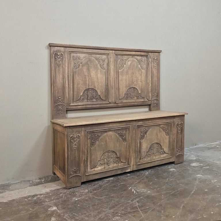 Charming 19th century country French stripped oak hall bench features a decidedly Baroque influence in the hand-carved bas relief that appears on the seat/trunk below and the seatback itself. Seat opens to reveal immense storage for blankets or