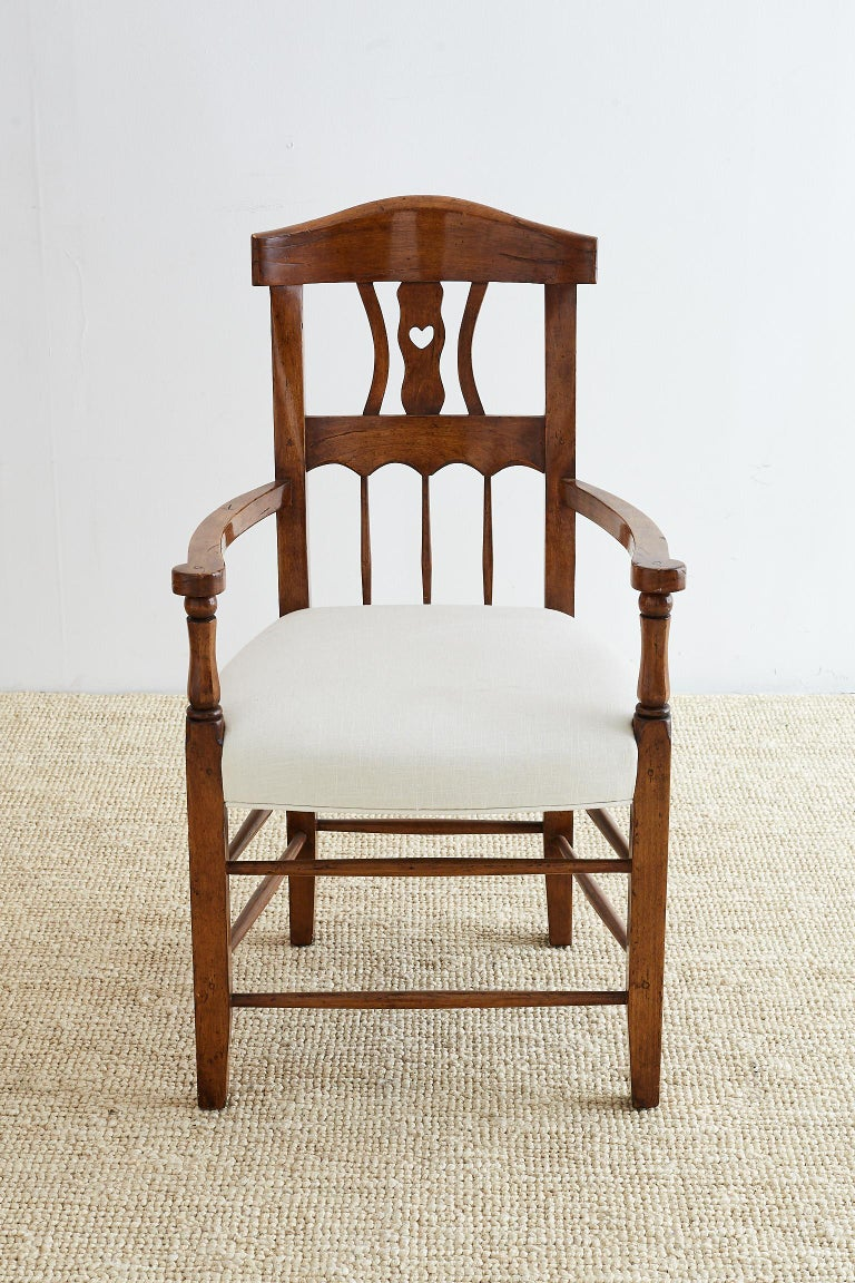 19th century French country armchair carved from fruitwood. Features a curved back with a whimsical carved heart backsplat. Constructed with wood peg joinery and newly upholstered in white linen. Recently renovated and finished in a rich dark stain.