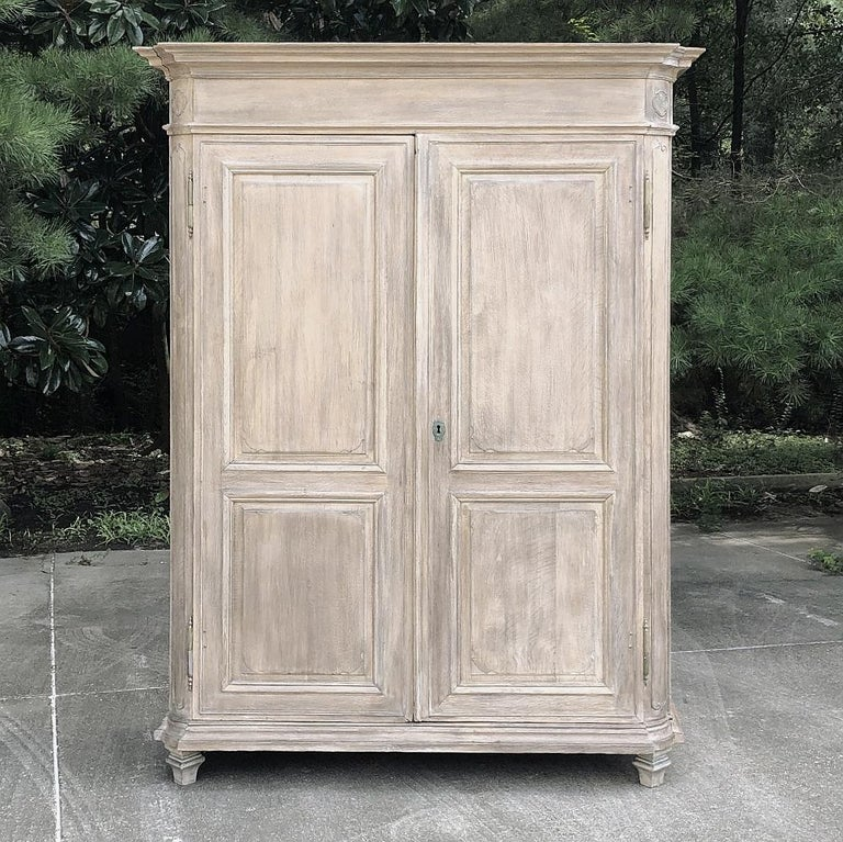 19th Century country French neoclassical whitewashed armoire is a majestic example of the revival of architecture that dates back to ancient Greece and Rome! The tailored design is enhanced by mitered corner posts that are also rounded, and the