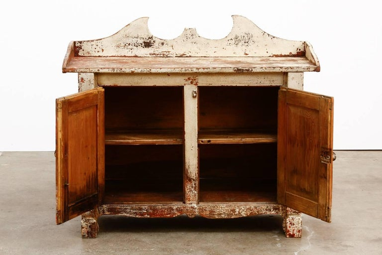 Rustic 19th century country French pine washstand cabinet featuring a painted finish that has been scraped down leaving a beautiful distressed patina with craquelure detail. The galleried top has a decorative broken pediment back splash and the case