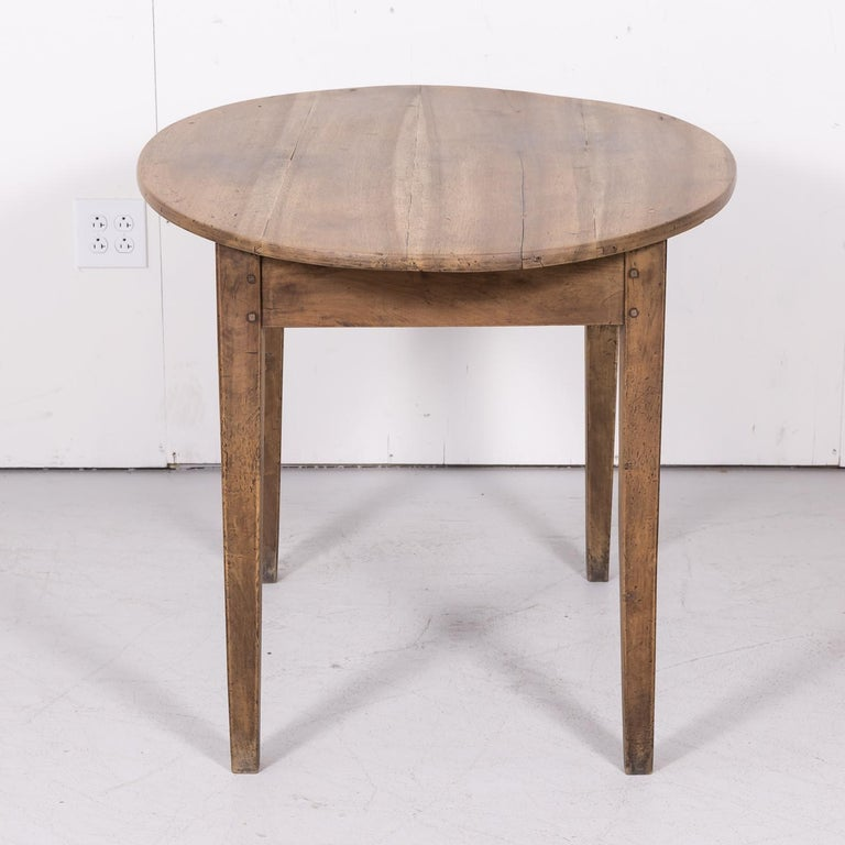 19th century Country French oval side table handcrafted in Lyon of solid walnut that has been bleached or washed to a natural finish and hand waxed to a beautiful patina, circa 1870s. Having an oval plank top over a single divided drawer, this