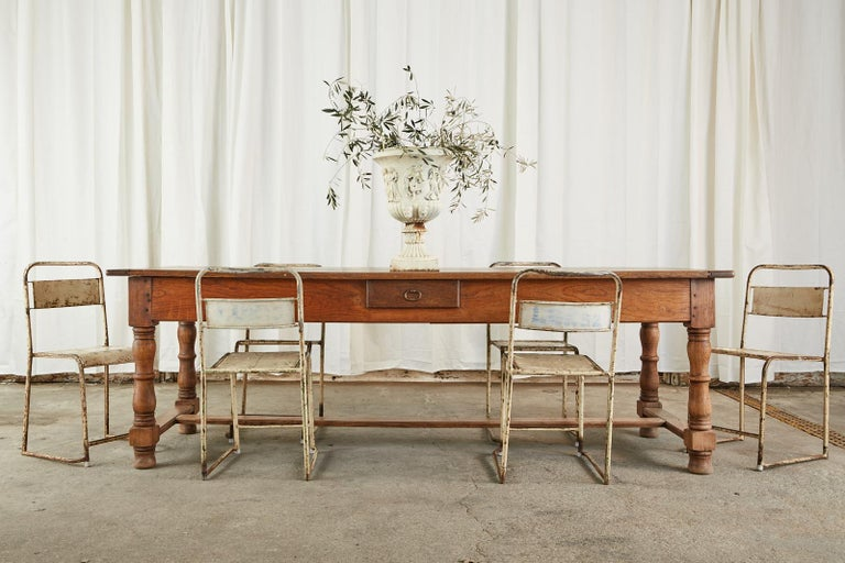 Quintessential 19th century country French Provincial farmhouse table or harvest dining table. The top was crafted from thick oak planks having tongue and groove breadboard ends. The table has large storage drawers on each end and a small storage