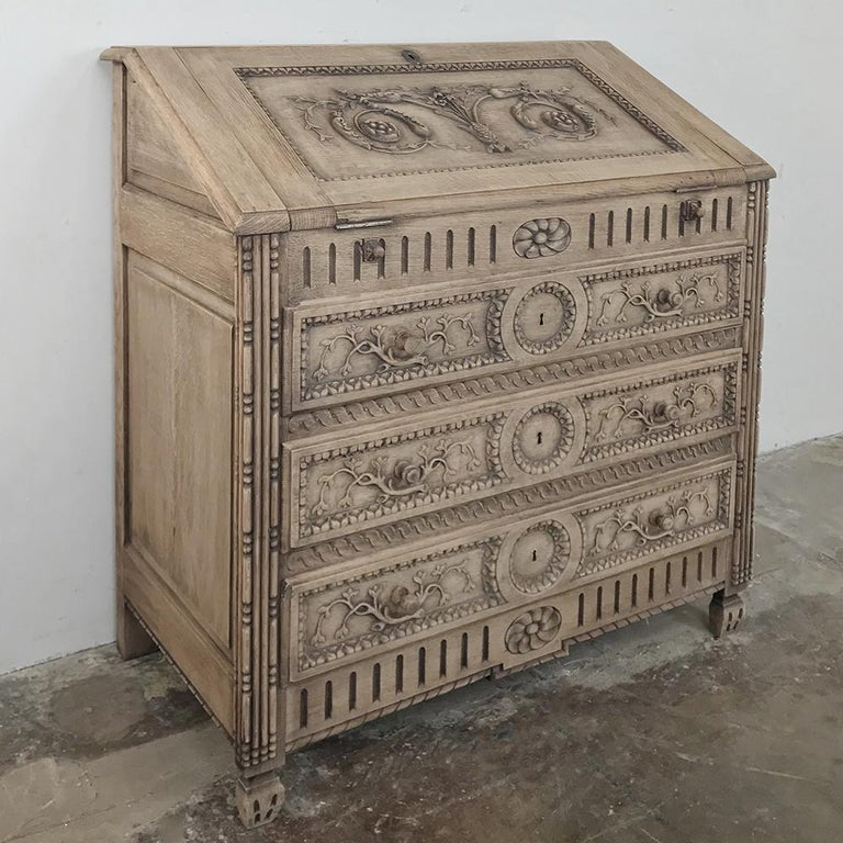 19th century Country French provincial stripped oak secretary is a delightfully hand carved expression of rural artisanry that also represents an exceptional workstation and storage in the chest pf drawers that will add as much panache to your decor