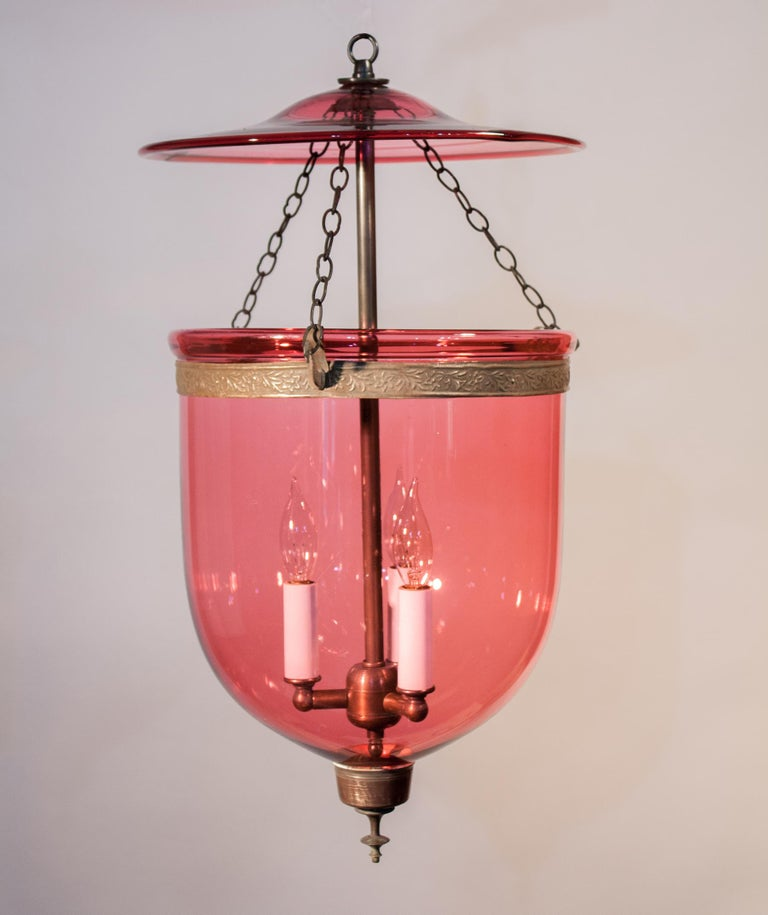 Magnificent is the word to describe this circa 1870 handblown cranberry glass bell jar lantern from England. Adorned with its original brass band and finial base, this versatilely-sized pendant will cast a warm, beautiful light in most any room or