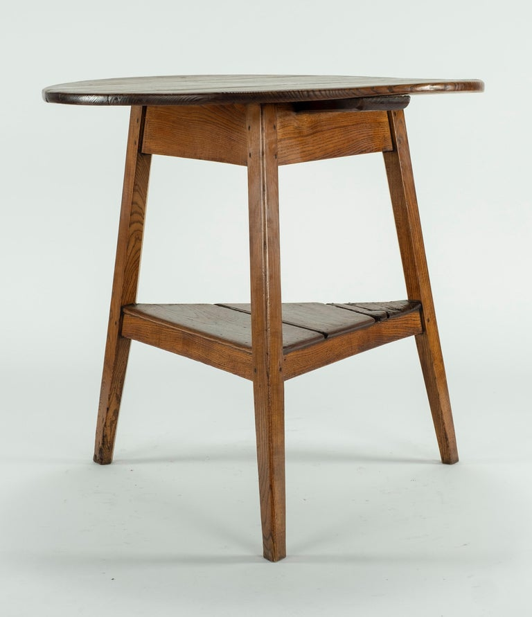 19th century elm table with tapering legs and an under shelf.