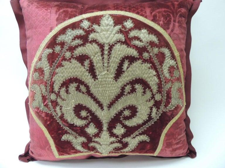 19th century red and gold crest applique velvet square decorative pillow.  19th century Persian gold and velvet embroidery applied onto 18th century red silk gaufrage velvet.  Decorative pillow framed with small antique metallic threads trim.