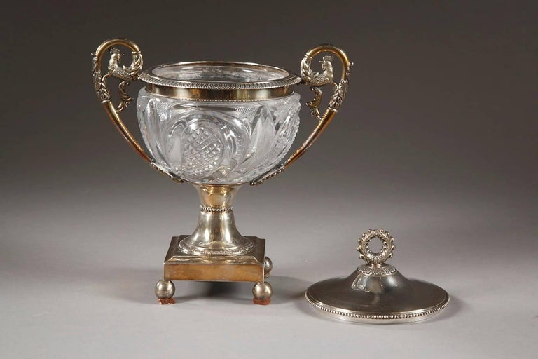 Elegant candy dish in Creusot cut crystal and silver, decorated with foliage and petals. The high handles are embellished with palmettes, acanthus leaves, and the final spiral finishes in the shape of a rooster. A crown-shaped knob adorns the top of