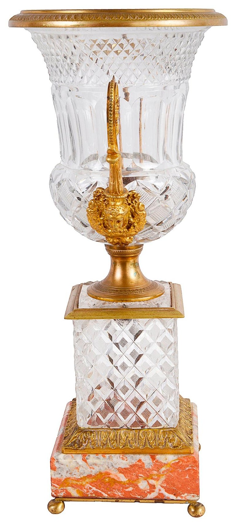 A good quality late 19th century ormolu mounted cut glass urn, having hob nail cut pattern, scrolling foliate twin handles with classical female mask mounts to the base of them. Having a pedestal base, hob nail cut glass plinth, raised on rouge