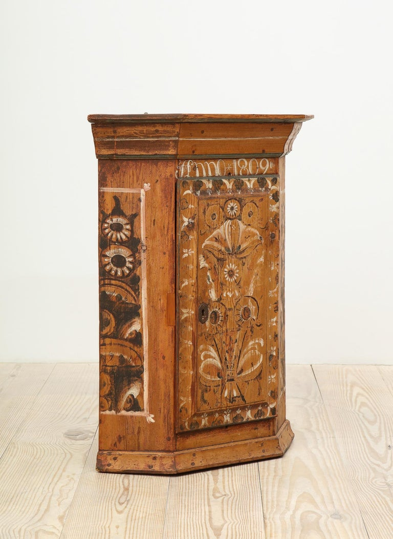 Exceptional 19th century Swedish Dalarna Allmoge corner cabinet painted with Kurbits / Rosemaling with center door, Dalarna, Sweden, inscribed and dated: Anno 1830; all original painting.  This corner cabinet, dated 1830, reflects the beautiful,
